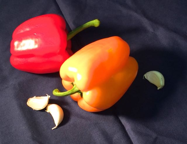 Pastel demo set up of two peppers and garlic cloves